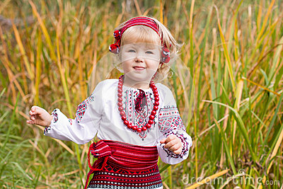Beautiful girl in ukrainian costume in a field