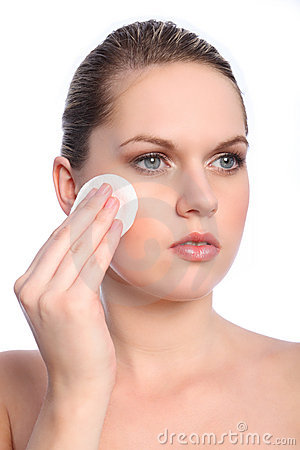 Beautiful girl using cosmetics cotton pad on face