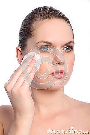 Beautiful girl using cosmetics cotton pad on face