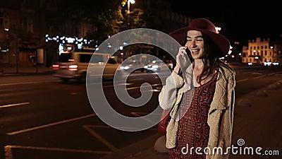 Beautiful girl using smortphone on street at night stock footage