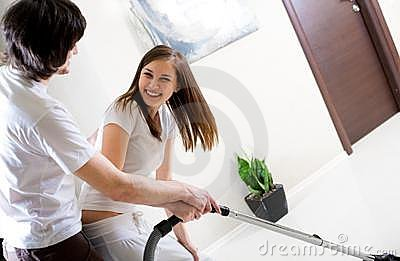 Beautiful girl with vacuum cleaner and boy
