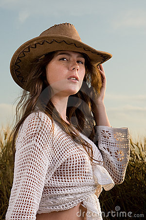 Beautiful girl in wheat field on sunset