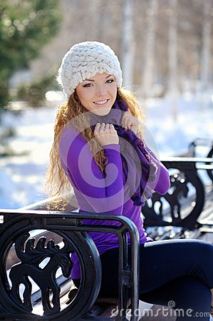 Beautiful girl in white knitted hat sitting on a bench in winter