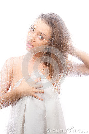 Beautiful girl in a white sheet behind a wet glass