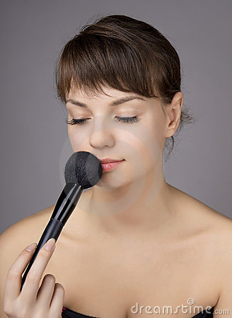 Beautiful girl who does make-up brush