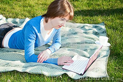 Beautiful girl working on laptop in the park