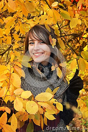 Beautiful girl among yellow autumn leaves