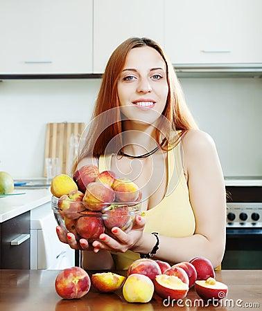 Beautiful girl in yellow holding peaches