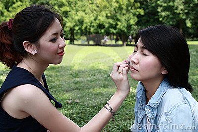 Beautiful girls helping their friend to makeup