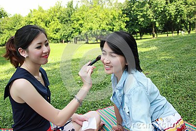 Beautiful girls helping their friend to makeup