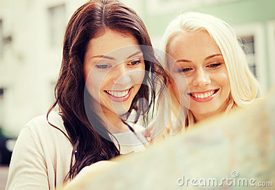 Beautiful girls looking into tourist map in city