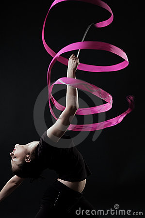 Beautiful gymnast with pink ribbon