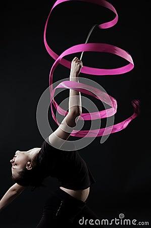 Beautiful gymnast with pink ribbon