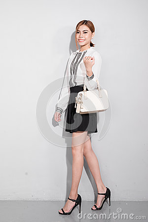 Free Beautiful Happy Asian Woman Holding A Bag Walking Over Gray Back Stock Image - 88469941