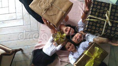 Beautiful happy family mother, father, son, and daughter with gifts in the hands are on the floor stock footage