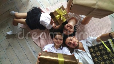 Beautiful happy family mother, father, son, and daughter with gifts in the hands are on the floor stock video