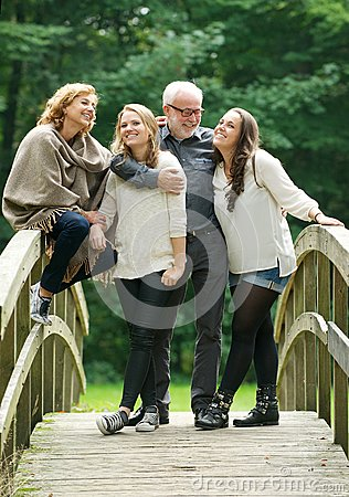 Beautiful happy family standing together in a bridge in the woods
