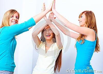 Beautiful happy girls giving five