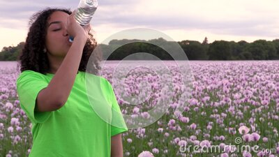 Mixed race African American girl teenager female young woman walking in field of pink poppy flowers drinking a bottle of water stock video footage