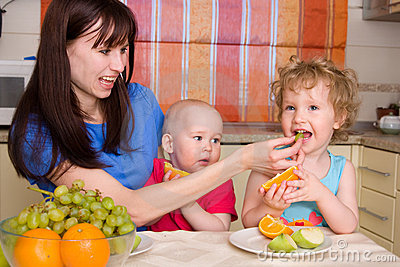 Beautiful happy mum with children eat fruit