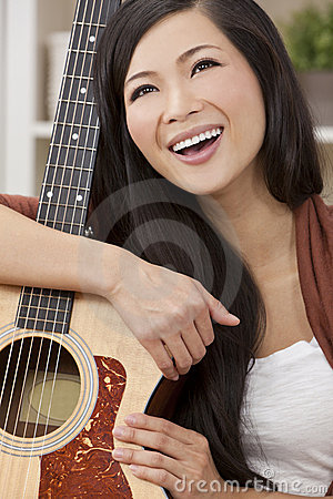 Beautiful Happy Oriental Woman Smiling & Guitar