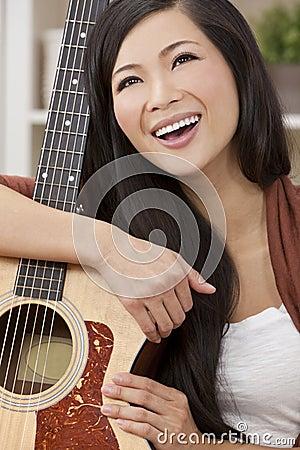 Beautiful Happy Oriental Woman Smiling & Guitar