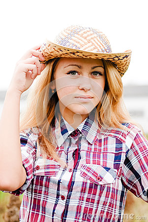 Pretty smiling happy blond teenage girl in cowboy hat