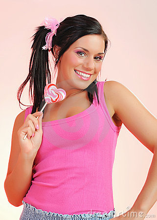 Beautiful happy teenage girl with a lollipop