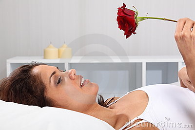 Beautiful happy woman in bed holding a red rose