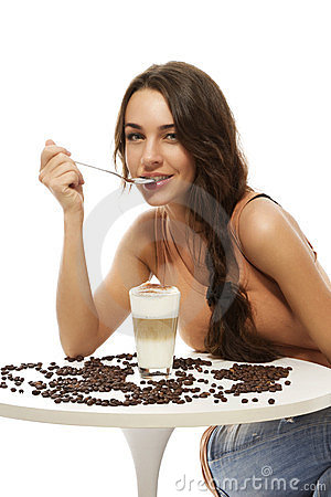 Beautiful happy woman at a table with latte