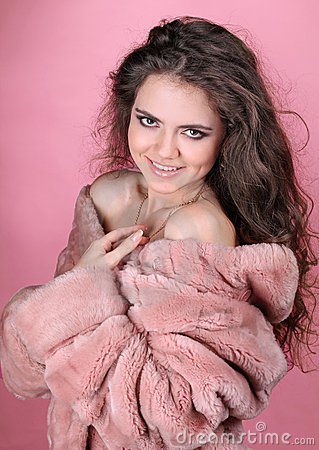 Beautiful happy woman in winter fur coat over pink