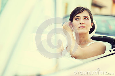 Beautiful happy young bride looking from red retro auto car