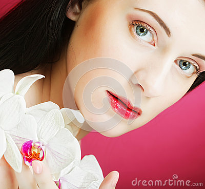 Beautiful healthy woman with orchid flower.