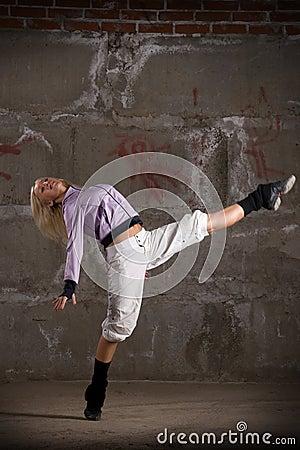Beautiful hip hop girl dancing over grey wall