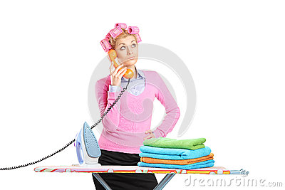 Beautiful housewife with hair rollers and telephone standing