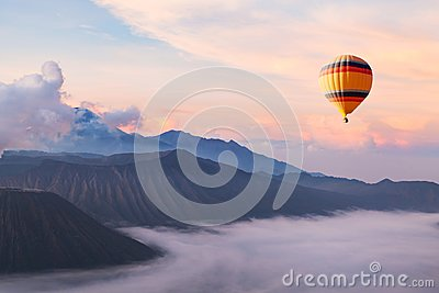 Beautiful inspirational landscape with hot air balloon flying in the sky, travel Stock Photo