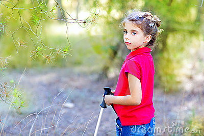 Beautiful kid girl trekking in park forest