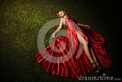 Beautiful Lady In Red Dress Lying On Grass
