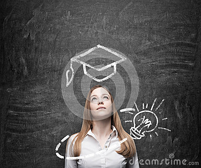 Beautiful lady is thinking about education. A graduation hat and a light bulb are drawn on the chalkboard above the lady. Stock Photo