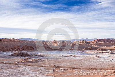 Beautiful landscape with red rocks, clouds and blue sky at Valle de La Luna during sunset