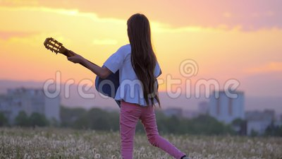 Beautiful landscape view at sunset. funny little girl musician playing the guitar walks outdoors dandelions field away from town b. Beautiful landscape view at stock video footage