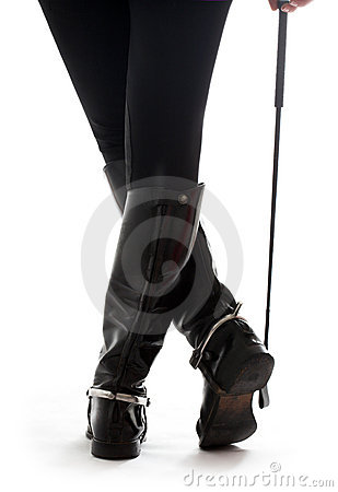 Beautiful legs in black leather horseman boots with riding-crop