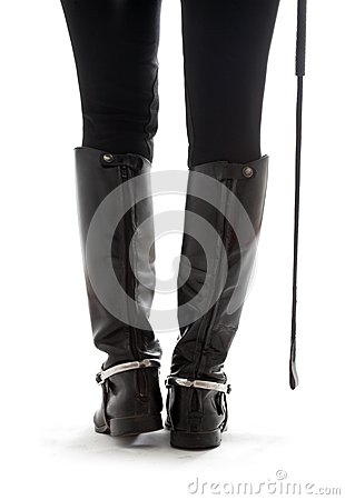 Beautiful legs in black leather horseman boots
