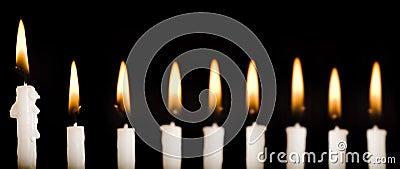 Beautiful lit hanukkah candles on black.