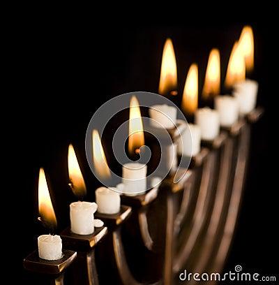 Beautiful lit hanukkah menorah on black.