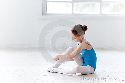 Beautiful little ballerina in blue dress for dancing for Dance where you sit on the floor