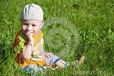 Beautiful little boy looks in green  meadow