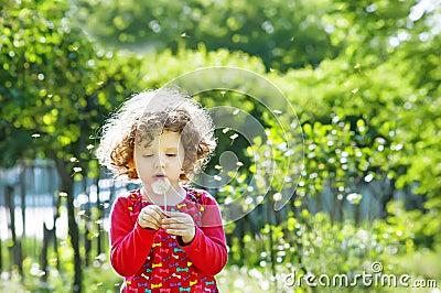 Beautiful little curly girl blowing dandelion, vertical shot