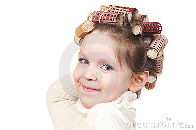 Beautiful little girl with curlers on her head.
