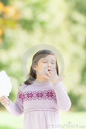 Beautiful little girl eating cotton candy in park.